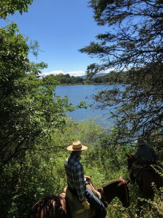 On horseback, Bill surveys a man-made lake